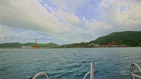 Boat with Head Rails Speeds across Azure Sea to Green Island Footage