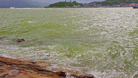 Azure Sea Waves Break at Rocky Bank against Cloudy Sky Footage