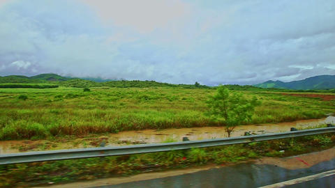Rural Landscape Fields Grass Road Barriers against Cloudy Sky Live Action