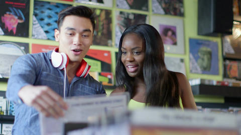 Upward Panning MS A Young Woman and Young Man flick through vintage records toge Live Action