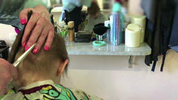 The hairdresser cuts the child