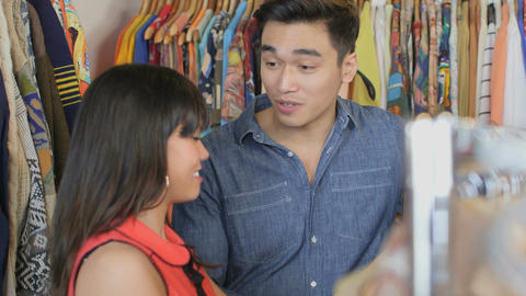 MCU A Young Woman and a young Man browse through a shop of colourful vintage clo Live Action