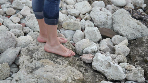 Female bare feet step on stones on the shore Stock Video Footage