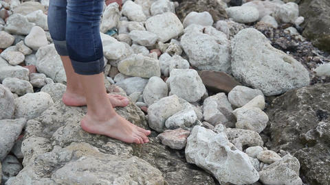 Female bare feet step on stones on the shore Live Action