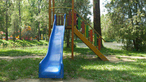 Young happy boy playing in public park on a slide Footage