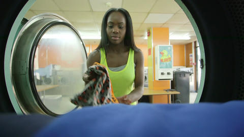 MS A Young Woman retrieves her laundry from the machine Footage