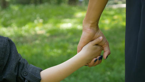 Closeup of child grabbing and holding mother hand Footage