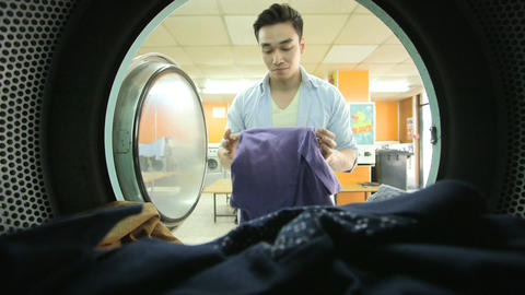 MS A Young Man collects his laundry in the Launderette Footage