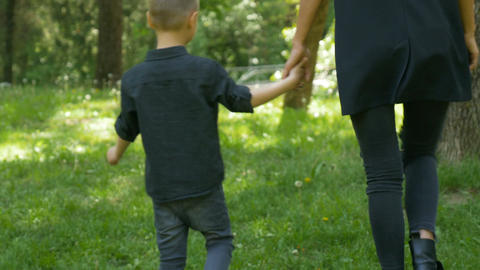 Mom and kid walking together holding hands in the park Footage