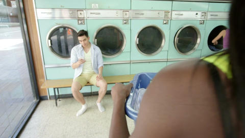 Female walks in to laundrette with laundry Filmmaterial