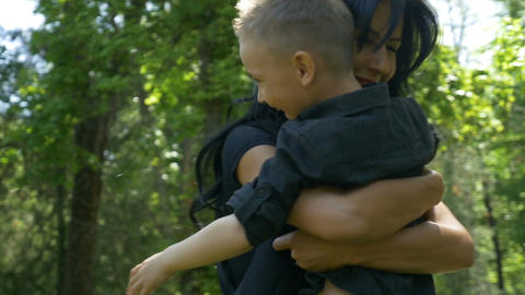 Young mother hugging and rotating her son slow motion in nature Footage