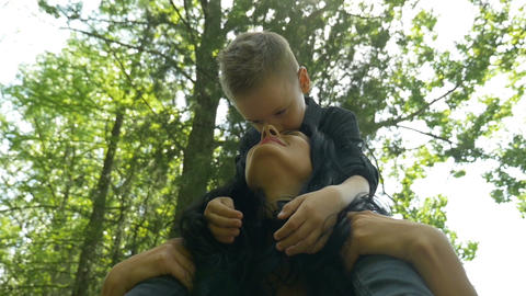 Young beautiful mom carrying her happy son on her shoulders with trees in backgr Footage