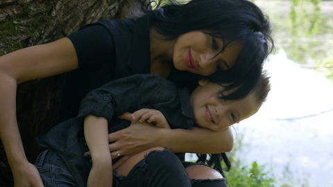 Attractive woman hugging and caressing her child sitting near a lake in the park Footage