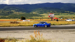 Blue racing car drifting the turn during a race