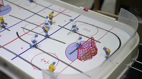 Person playing table ice hockey, hitting puck into opposing net, indoor activity Footage