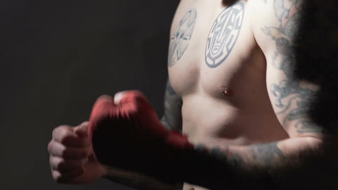 Strong Muay Thai boxer with tattoos training before fight in the gym, slowmotion Footage