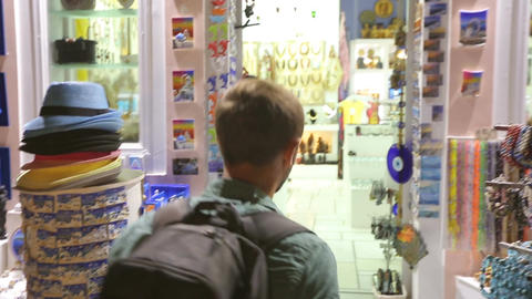 Male tourist coming to souvenir shop, choosing gifts with happy smile on face Footage