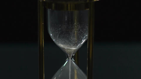 Last grains of sand running out in vintage hourglass, wasted time, transiency Footage