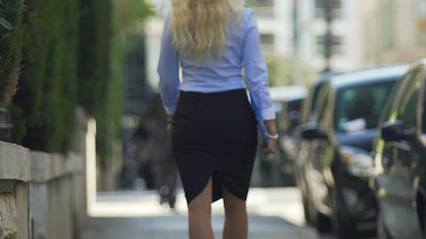 Sexy blonde lady with beautiful gait slowly walking along street to her work Footage