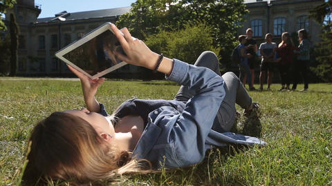 Cute female student studying with tablet in park Footage