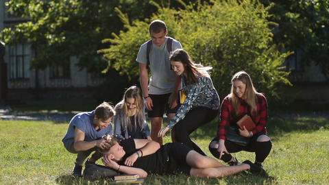 Group of students waking up sleepy friend in park Footage