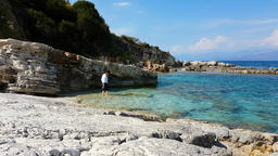 Woman on the beautiful natural rock beach of Kassiopi, Corfu Island, Greece, Ion Filmmaterial