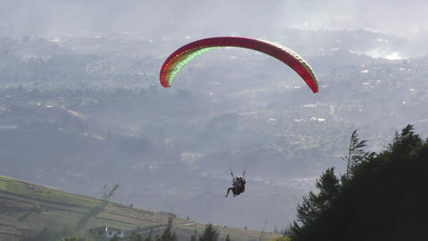 rainbow colored paraglide flying at low altitude Footage