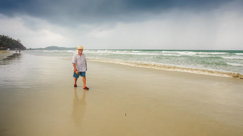 Bearded Old Man in Hat Goes along Wet Sand by Wave Surf Footage