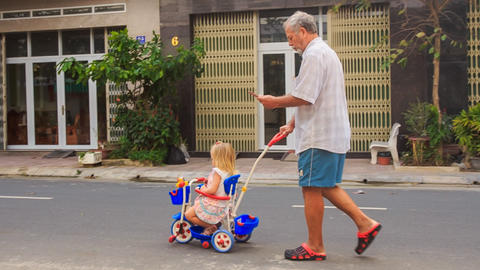 Grandpa Pushes Tricycle with Little Girl Reads Smartphone Footage