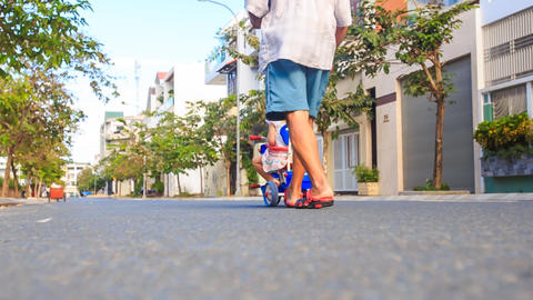Backside Grandpa Pushes Tricycle with Girl Reads Ipod Footage
