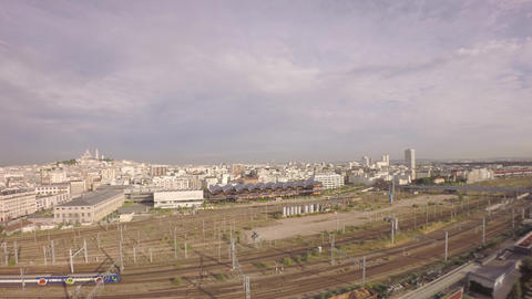 Aerial view of TGV high speed train passing at Gare du Nord and tilt up of city  Footage