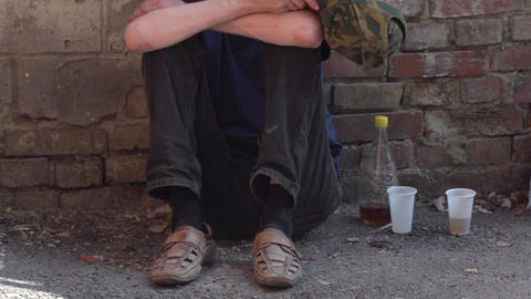 a young man sitting on the ground against the wall with a bottle of alcohol Footage