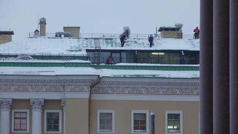 Cleaners on roof, remove snowdrift using snow shovel, time lapse shot Footage