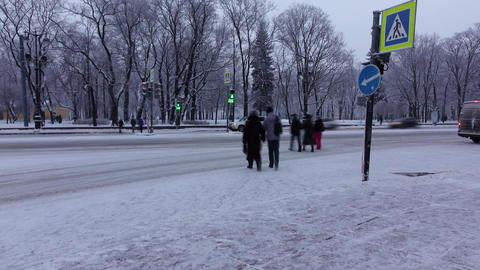Pedestrians cross at snowy street, time lapse shot, Dim evening light Footage