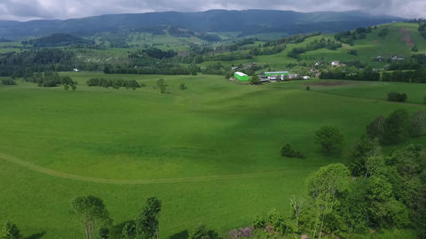 Aerial View. Sunset. Flight over a green grassy hills Footage