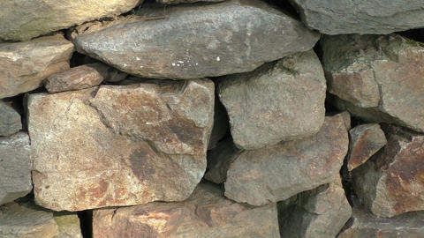 Wall of stacked slabs of stone. Dry wall built without mortar. Detail close up