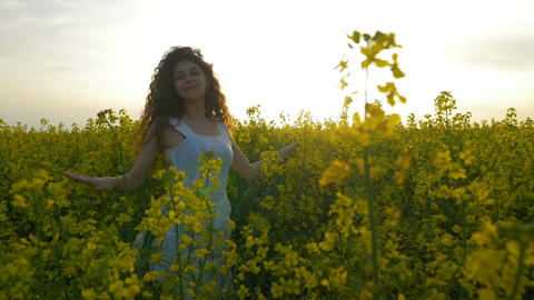 Young woman dancing and spinning in the canola flowers enjoying herself before t Footage