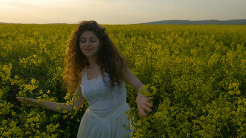 Happy curly girl dancing in rapeseed field enjoying summer at sunset Footage