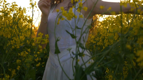 Joyful lady in white dress spinning in the rapeseed field holding a yellow flowe Footage