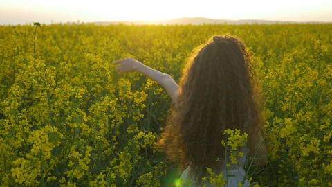 Slow motion of young woman with white dress dancing in the field full of canola  Footage