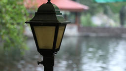 Garden lamp next to a pond in rainy day Footage