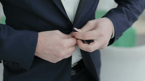 Buttoning a jacket. Stylish man in a suit fastening buttons on his jacket prepar Live Action