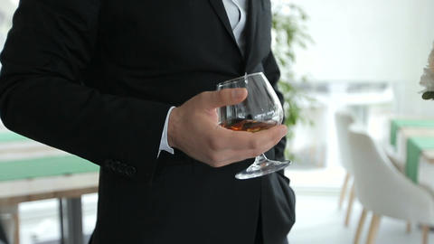 Groom holds in one hand a glass of whiskey ビデオ