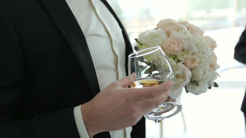 Groom holds in one hand a glass of whiskey and another bouquet for the bride