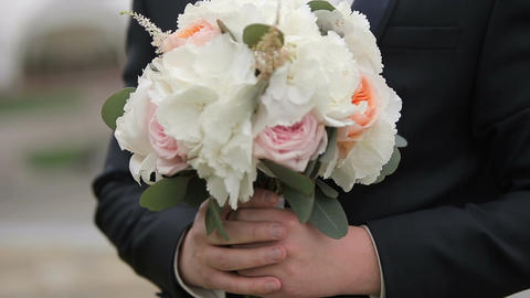 The groom holding a bouquet of flowers for the bride