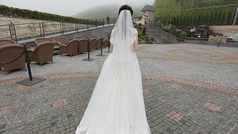 The bride in a beautiful long white dress walking to her husband Live Action