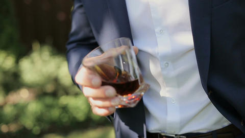 Groom holds on hand a glass of whiskey