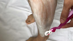 Woman shaves her hair on her leg 画像