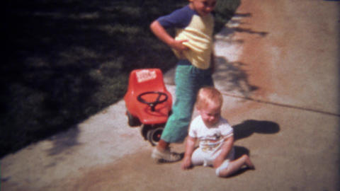 1979: Brother helps baby sister after play vehicle accident Footage
