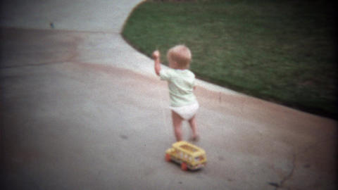 1979: Caucasian blonde toddler pulling school bus toy on sidewalk Live Action
